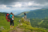 Man in montains is photographing — Stock Photo