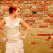 Bride near the brick wall - Stock Photo