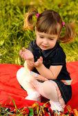 Little girl in garden talking on red carpet — Stock Photo