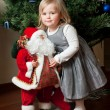 Cute little girl with toy Santa Claus — Stok fotoğraf