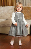 Cute little girl in a gray dress — Stock Photo