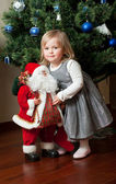 Cute little girl with toy Santa Claus — Stockfoto