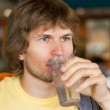 Handsome young man drinking water — Stock Photo