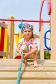 Pretty little girl on playground equipment — Stock Photo