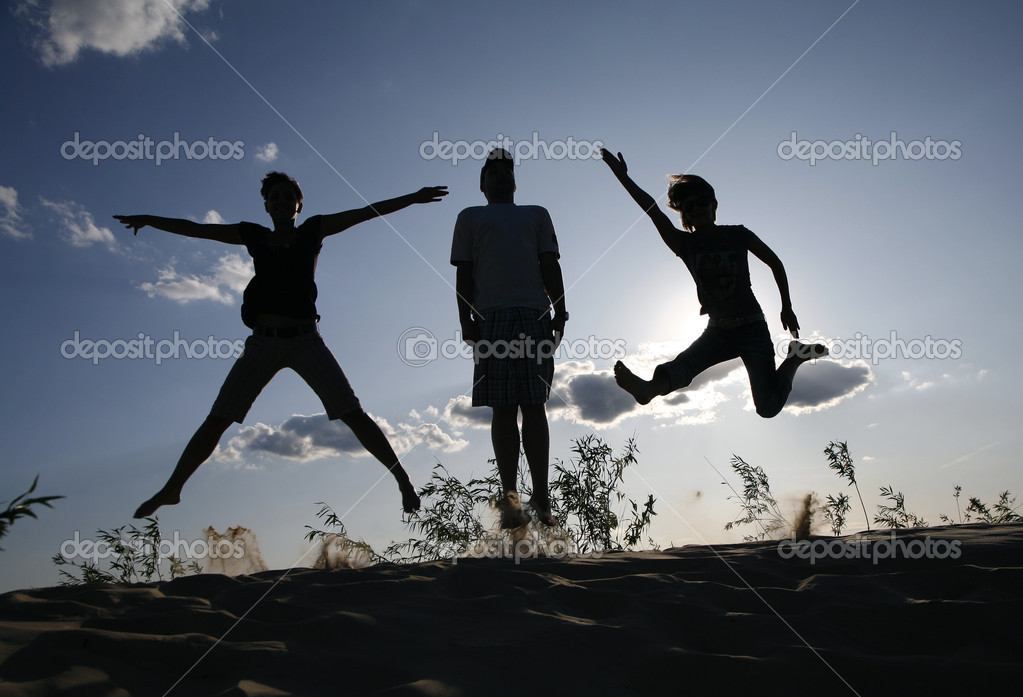 Group of three young jumping on a send hill  Stock Photo #2724299