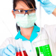 Scientist in laboratory with test tubes - Stock Photo