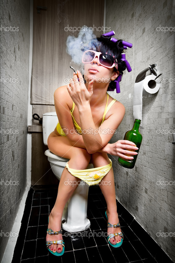 Girl sits in a toilet with an alcohol bottle — Stok fotoğraf #3773025