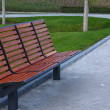 New wooden bench in a city park — Stock Photo