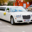 White wedding limousine on the road. Ornated with flowers. - Stock Photo