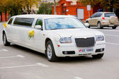 White wedding limousine on the road. Ornated with flowers. — Stock Photo