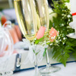 Champagne glasses with flowers on the background - Stock Photo