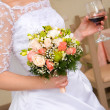 Bride with a wedding bouquet and glass of red wine - Photo
