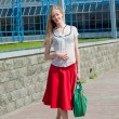 Smiling sexy blonde girl wearing red skirt with a green bag. In — Stock Photo