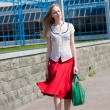 Smiling sexy blonde girl wearing red skirt with a green bag. In — Stock Photo #4707920