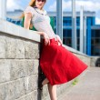 Smiling sexy blonde girl wearing red skirt. In all growth. Near — Stock Photo