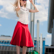 Young woman, blond, against the backdrop of the station. In all - Stockfoto