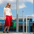 Smiling sexy blonde girl wearing red skirt with a green bag. In — Stock Photo #4707929