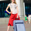 Smiling sexy blonde girl with blue suitcase — Stock Photo