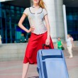 beautiful girl with a suitcase against the backdrop of the stati — Stock Photo