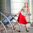 Beautiful girl, blond, pulls a suitcase against the backdrop of — Stock Photo