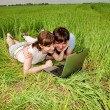 Casual happy couple on a laptop computer outdoors — Stock Photo #4708042
