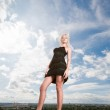 Beautiful girl stending against a cloudy sky — Stock Photo