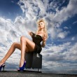 Beautiful girl sitting against a cloudy sky — Stock Photo