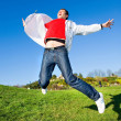 Happy young man - jumping end flies in blue sky — Stock Photo