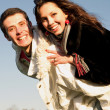 Happy young couple jumping in sky above a green meadow — Stock Photo #4708248
