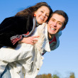 Young love couple smiling end fly under blue sky — Stock Photo