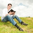 Royalty-Free Stock Photo: Happy man reading a book sitting on the green grass