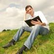 Happy man reading a book sitting on the green grass - Stock Photo