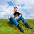 Young man sit in the park enjoying the fresh air and reading a b — Stock Photo