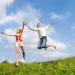 Happy Young Couple - jumping in the sky above a green meadow — Stock Photo #4708410
