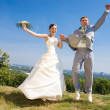 Groom and bride jumping against backdrop a sky and trees. In all — Stock Photo