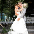 Groom and bride joy against backdrop fountain — Stock Photo #4708598