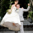 Groom and bride joy against backdrop fountain — Stock Photo