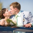 Bride and groom kissing on wedding auto — Stock Photo #4708615