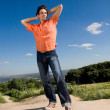 Young man winning on peak of a mountain. Against a blue sky with — Stock Photo
