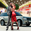 Stock Photo: Portrait Young love Couple smiling under Offroad luxury car, int