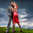 Young couple with storm cloudy sky — Stock Photo