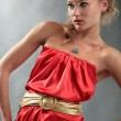 The beautiful blonde in a red dress and a gold belt looks forward — Stock Photo