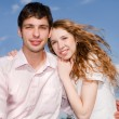 Portrait of a young happy couple against a backdrop of blue sky — Stock Photo