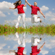 Stock Photo: Happy Young Couple - team is jumping