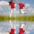 Happy Young Couple - team is jumping — Stock Photo