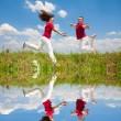 Happy smiling couple jumping in sky above a green meadow — Stock Photo #4709008