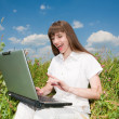 Young woman sitting on the grass field with a laptop. Against th — Stock Photo #4709077