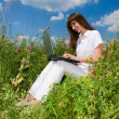 Young woman on the grass field with a laptop — Stock Photo