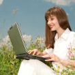 Happy Young Woman on the grass field with a laptop — Stock Photo #4709085