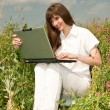 Happy Young Woman on the grass field with a laptop — Stock Photo #4709086